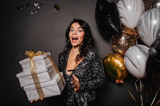 Zdziwiona wysportowana kobieta bawiąca się w czasie świąt bożego narodzenia