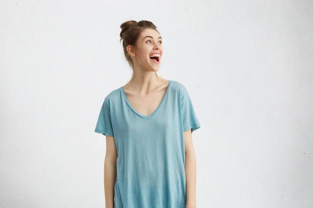 Zdziwiona, zafascynowana młoda kobieta rasy kaukaskiej w długiej koszulce wykrzykuje z podniecenia i zachwytu, otwierając szeroko otwarte usta, patrząc na pustą ścianę