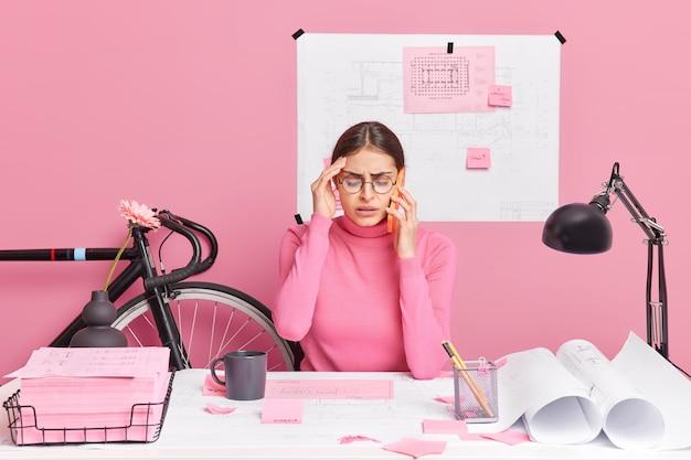 Zdziwiona, zajęta młoda kobieta ma termin ukończenia projektowania szkiców, boli ból głowy, dzwoni ktoś przez smartfona, czuje się wyczerpany, gdy ciężko pracuje nad projektem