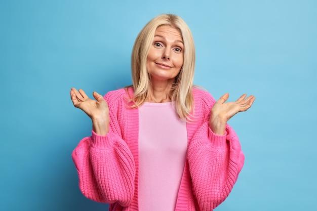 Zdziwiona, zakłopotana kobieta wzrusza ramionami, wygląda na wątpliwą i niepewnie rozważa, kiedy podejmuje decyzję ubrana w różowe ubranie.