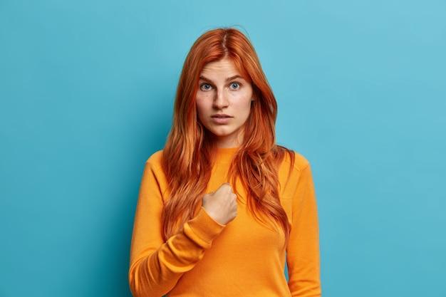 Zdziwiona zdezorientowana rudowłosa kobieta wskazuje na siebie i pyta, kto ja ubrany w zwykły pomarańczowy sweter, nie może zrozumieć, dlaczego wybrano ją jako ubraną niedbale.