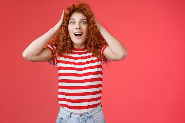 Zdziwiona zdziwiona emocjonalna szczęśliwa ruda dziewczyna otrzymuje niesamowitą ofertę prezent chwyć kręcone włosy otwarte usta uśmiech zdumiona oszołomiona niesamowita fajna okazja triumfująca na czerwonym tle.
