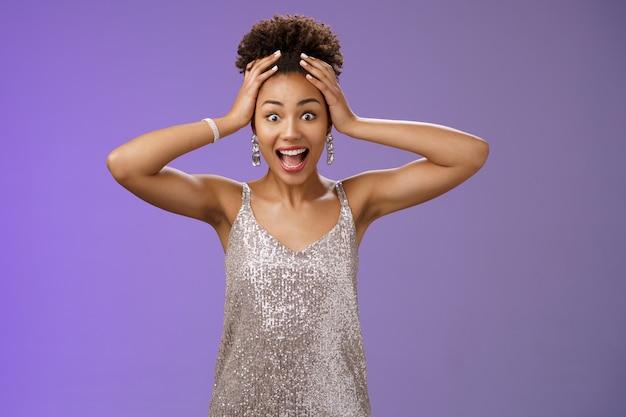 Zdziwiona zdziwiona podekscytowana afrykańsko-amerykańska kobieta wygrywająca na loterii nie może uwierzyć zachwycona trzymać głowę krzycząca rozbawiona uśmiechnięta zdumiona stojąca pod wrażeniem błyszczącej błyszczącej sukienki, niebieskie tło.