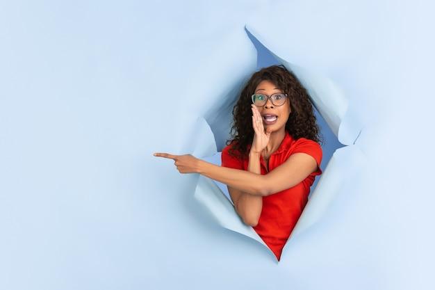 Zdziwiona, zdziwiona, wskazująca wesoła afroamerykanka w rozdartym niebieskim papierze