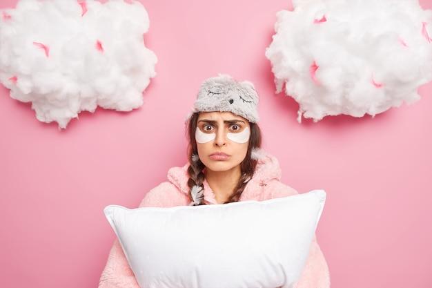 Zdziwiona zmartwiona kobieta budzi się z dwóch warkoczy po tym, jak koszmar trzyma miękką poduszkę