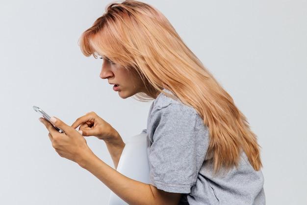 Zdziwiona zmieszana kobieta używa smartphone.