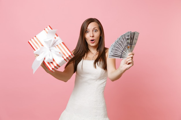 Zdziwiona, zszokowana kobieta w białej sukni, trzymająca mnóstwo dolarów, gotówkę, czerwone pudełko z prezentem, prezent