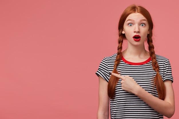 Zdziwiona zszokowana zmartwiona nastolatka z dwoma rudowłosymi warkoczami czerwona szminka otwarte usta w panice wskazujący palec po lewej stronie zwraca twoją uwagę na skopiowanie miejsca, zmartwiona zdziwiona różową ścianą