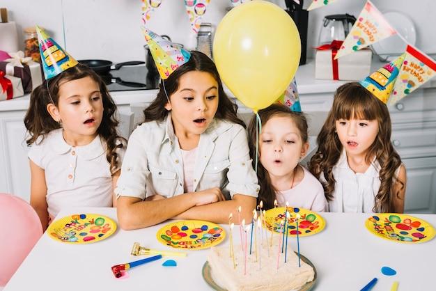 Zdziwione dziewczyny patrzeje urodzinowego tort z iluminującymi świeczkami i kolor żółty balonami