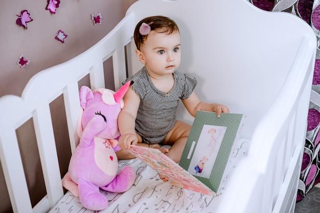 Zdziwione, urocze dziecko otwierające swój album ze zdjęciami w łóżeczku i uważnie przyglądające się mamie