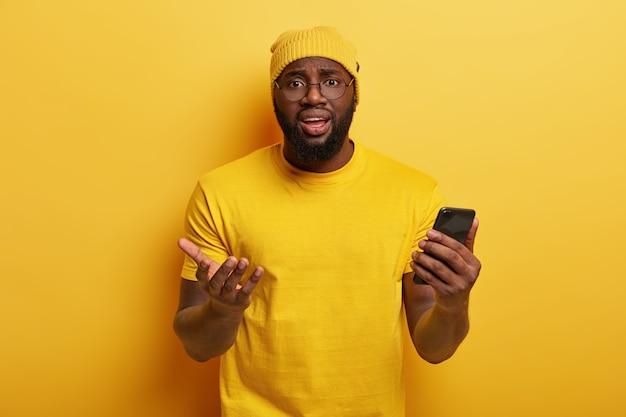 Zdziwiony afro amerykanin ma sfrustrowany wyraz twarzy, trzyma nowoczesną komórkę