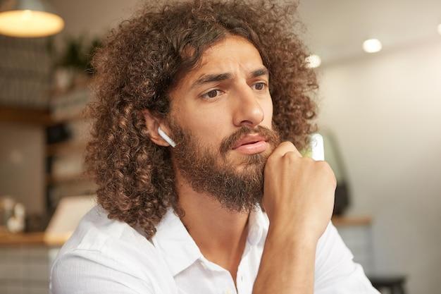 Zdziwiony atrakcyjny mężczyzna z kręconymi włosami, z bujną brodą, oparty na brodzie i wyglądający na oszołomionego, marszczący brwi i myślący o czymś ważnym, pozujący nad wnętrzem