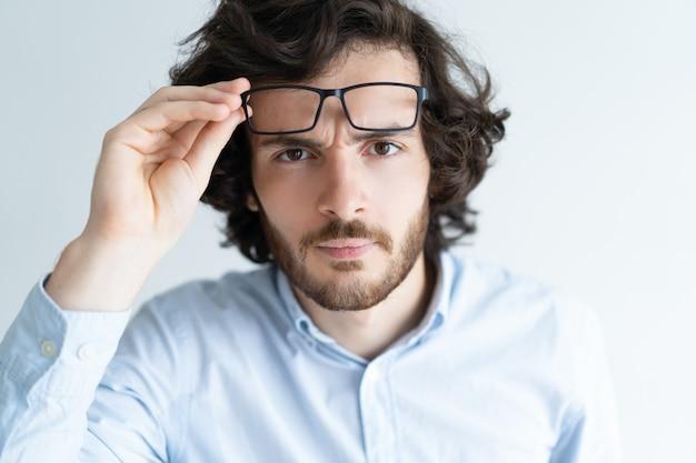 Zdziwiony atrakcyjny młody człowiek gapi się przy kamerą