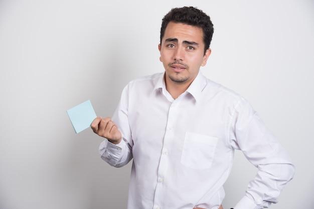 Zdziwiony biznesmen trzymając bloki notatek na białym tle.
