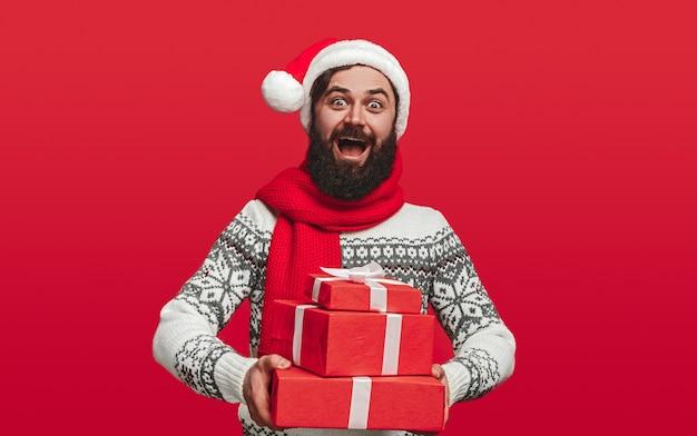 Zdziwiony brodaty hipster w czapce świętego mikołaja niosący stos pudełek z prezentami
