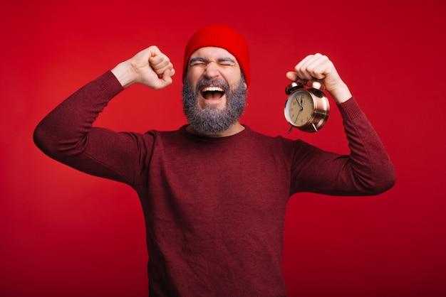 Zdziwiony brodaty mężczyzna hipster jest gotowy do świętowania nowego roku