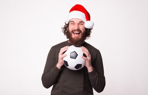 Zdziwiony brodaty mężczyzna trzyma piłkę nożną, krzyczy i nosi kapelusz świętego mikołaja