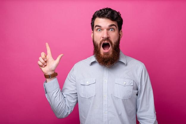 Zdziwiony brodaty mężczyzna w koszuli wskazujący na copyspace