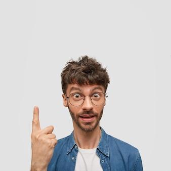 Zdziwiony, brodaty młody mężczyzna trzyma w górze palec wskazujący