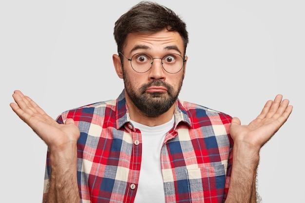 Zdziwiony, brodaty młody mężczyzna wygląda z zaskoczeniem i wahaniem, wzrusza ramionami w oszołomieniu