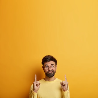 Zdziwiony, brodaty młody mężczyzna ze zdezorientowanym wyrazem twarzy, wskazuje w górę dwoma palcami wskazującymi, patrzy w górę, stoi zaniepokojony, zastanawia się nad najnowszymi cenami, nosi żółty sweter, przezroczyste okulary