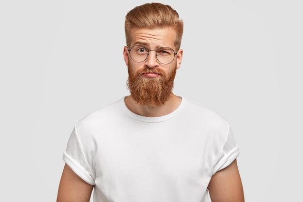 Zdziwiony brodaty rudy mężczyzna unosi brwi w zdumieniu, słyszy coś nieoczekiwanego od przyjaciela