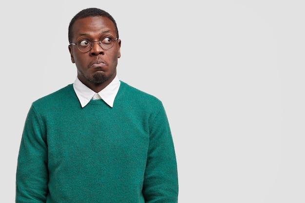 Zdziwiony ciemnoskóry mężczyzna wygląda zamyślony i oszołomiony, skupiony na boku, ubrany w swobodny sweter