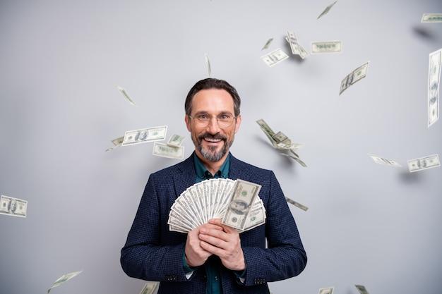 Zdziwiony dojrzały biznesmen pokazuje pieniądze z latającymi dolcami