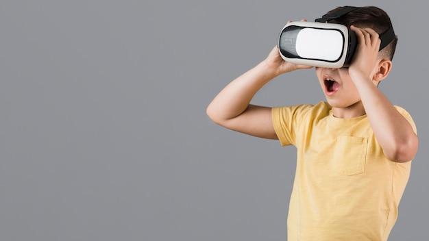 Zdziwiony dzieciak używa wirtualnej rzeczywistości słuchawki z kopii przestrzenią