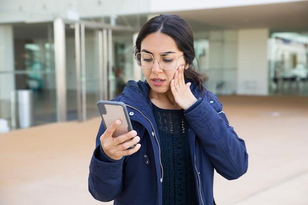 Zdziwiony dziewczyny czytanie na smartphone ekranie