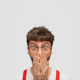 Zdziwiony europejczyk zakrywa usta, ma przerażony wyraz, patrzy oczami pełnymi niedowierzania
