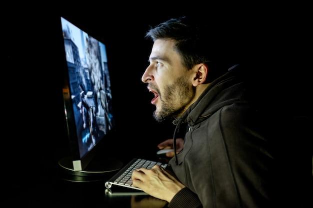 Zdziwiony facet emocjonalnie grający w grę komputerową