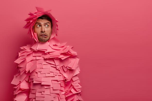 Zdziwiony facet gdzieś skoncentrowany, myśli, jak rozwiązać sytuację, ma oburzony wyraz twarzy, zaciska usta, pokryty różowymi naklejkami wokół głowy i ciała, skopiuj miejsce na tekst promocyjny