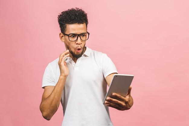 Zdziwiony facet korzystający z cyfrowego tabletu, zszokowany wiadomościami z mediów społecznościowych