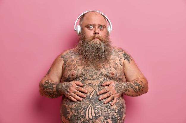 Zdziwiony facet trzyma ręce na brzuchu, ma wytatuowany brzuch i ramiona, stoi nagim ciałem, ma nadwagę, słucha ulubionego utworu w słuchawkach, odizolowany na różowej ścianie.