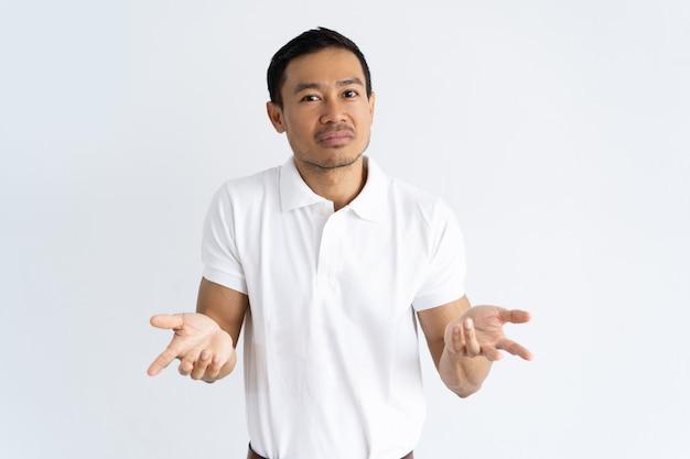 Zdziwiony facet wzrusza ramionami