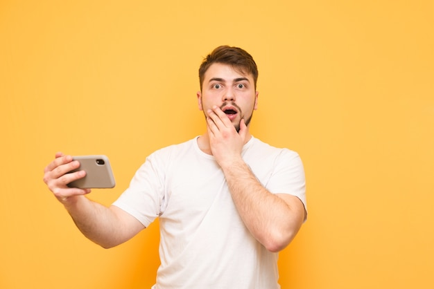 Zdziwiony gracz ze smartfonem w dłoniach na żółtym tle