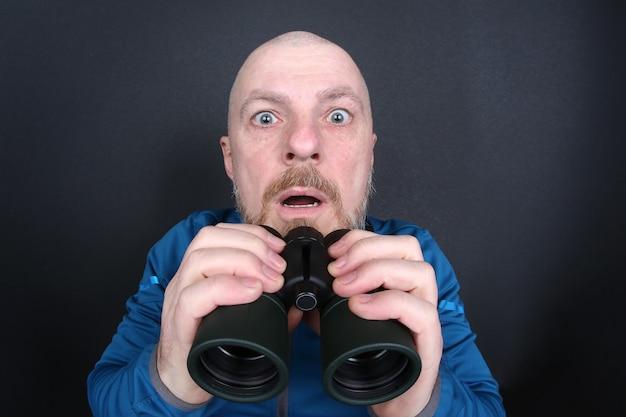 Zdziwiony i przestraszony brodaty mężczyzna z lornetką w dłoniach na szarym tle