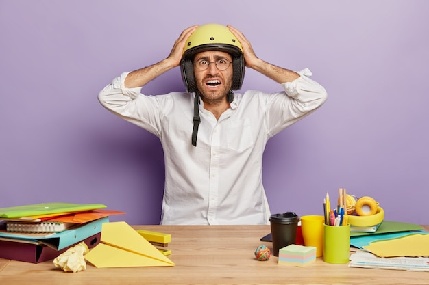 Zdziwiony kłopotliwy pracownik siedzący przy biurku