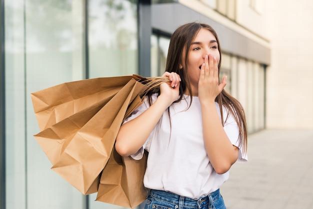 Zdziwiony kupujący otwierający usta, trzymający torby z zakupami, oglądający promocje w sklepach i wskazujący na ulicę