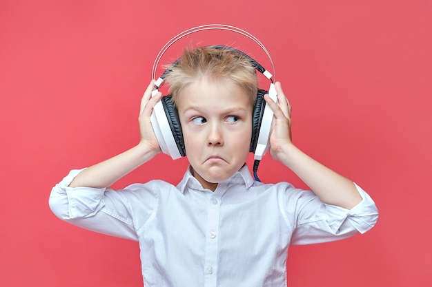 Zdziwiony mały chłopiec w słuchawkach na czerwono