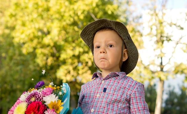 Zdziwiony mały chłopiec wyciągający zabawny wyraz twarzy trzymający bukiet kwiatów dla swojej matki