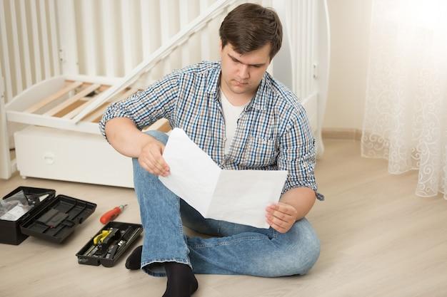 Zdziwiony mężczyzna czytający instrukcję montażu łóżeczka dla dziecka