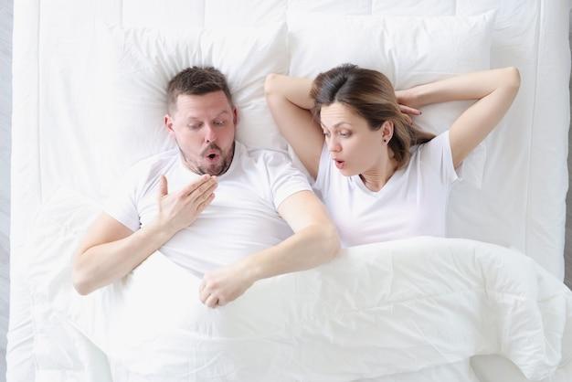 Zdziwiony mężczyzna i kobieta wyglądają pod osłonami koncepcji rozmiaru męskiego penisa