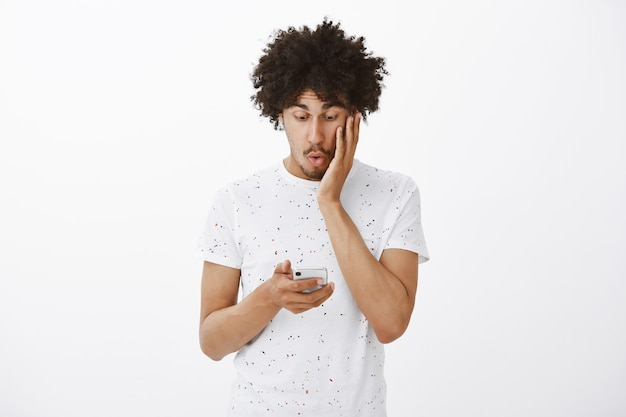 Zdziwiony mężczyzna patrząc na telefon komórkowy zdumiony i podekscytowany