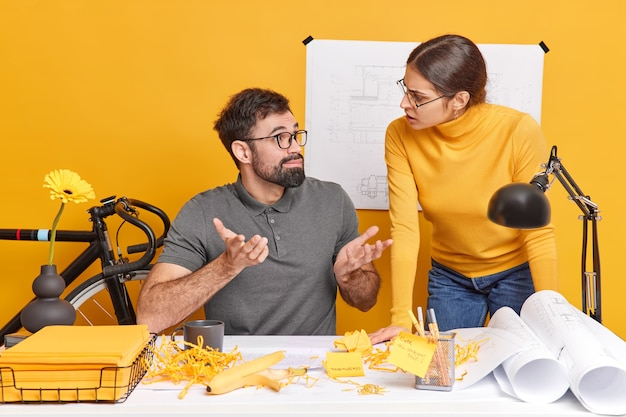 Zdziwiony mężczyzna patrzy na koleżankę ze zdezorientowanym wyrazem twarzy, wzrusza ramionami, nie wie, jak poprawić szkic do projektu budowlanego, omawia ważne kwestie związane z pracą, spróbuj znaleźć wspólne rozwiązanie