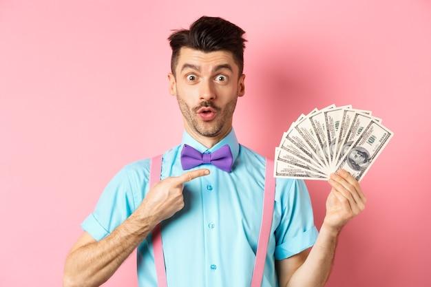 """Zdziwiony mężczyzna pokazujący dużą nagrodę pieniężną, wskazujący na dolary i mówiący """"wow"""", patrzy pod wrażeniem na aparat, stojąc na różowym tle."""
