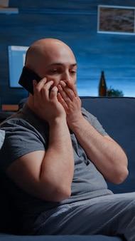Zdziwiony mężczyzna rozmawia przez telefon i odbiera okropne wiadomości