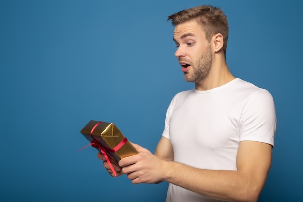 Zdziwiony mężczyzna trzyma złotego prezent odizolowywający na błękicie