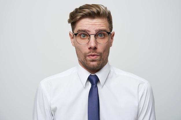 Zdziwiony mężczyzna ubrał białą koszulę i krawat